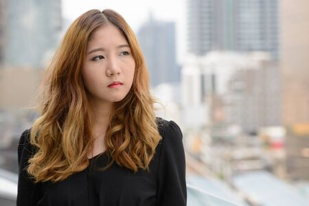 Face of young beautiful Asian businesswoman thinking in the city Stockfoto