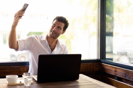 Portrait of happy Turkish man taking selfie at the coffee shop