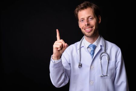 Portrait of happy bearded man doctor pointing up