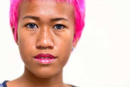 Face of young rebellious Asian woman with pink hair and nose piercing