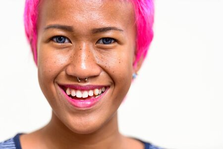 Face of happy young rebellious Asian woman with pink hair smiling