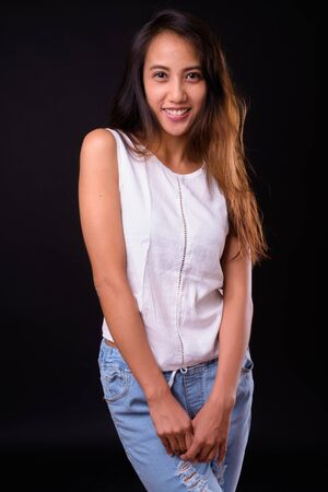 Young beautiful Asian woman against black background