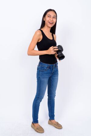 Full body shot of young Asian woman with camera