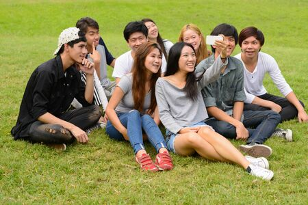 Happy young group of friends taking selfie together at the park Stockfoto