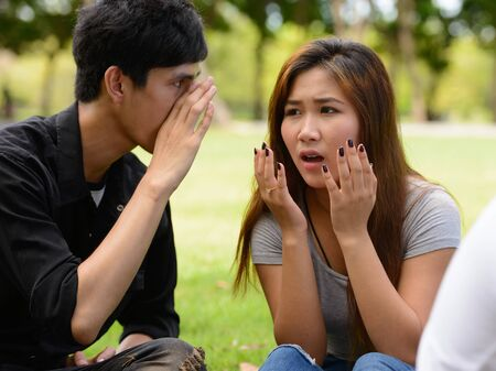 Two young Asian friends whispering together at the park Imagens