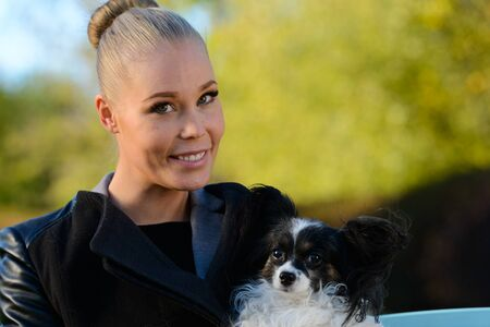 Close up of young happy woman smiling while holding cute dog and sitting on bench in the park Stockfoto