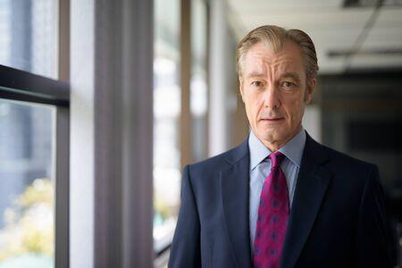 Hombre de negocios guapo maduro en traje junto a la ventana en el trabajo