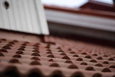 Portrait of roof constructed with brown tiles as exterior of the house