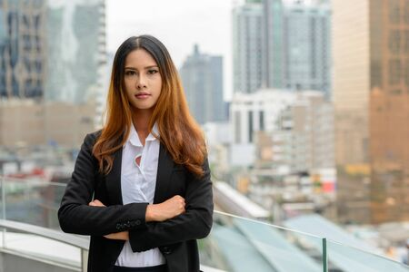 Young beautiful Asian businesswoman against view of the city