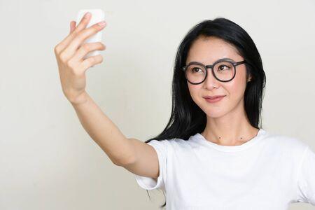 Portrait of young beautiful Asian nerd woman taking selfie Imagens