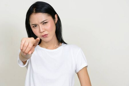 Portrait of stressed young Asian woman pointing at camera