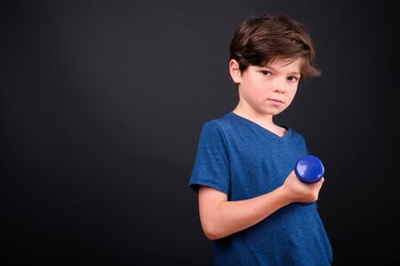 Portrait of young handsome boy exercising with dumbbells