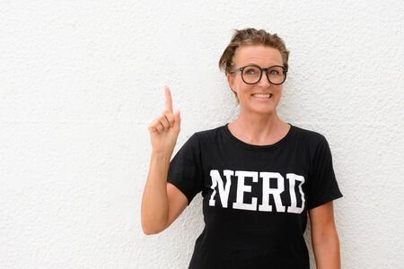 Happy mature nerd woman wearing big eyeglasses and standing against white background outdoors while smiling and pointing finger up