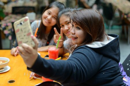 Group of young Asian women as friends taking selfie together outdoors