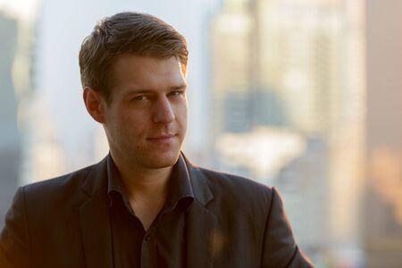 Cara de joven empresario guapo contra la vista de la ciudad