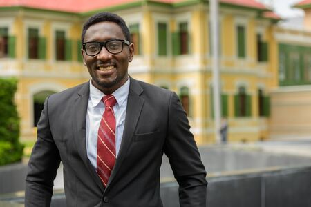 Happy young African businessman with eyeglasses smiling in the city streets outdoors