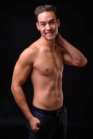Young handsome multi ethnic man shirtless against black background