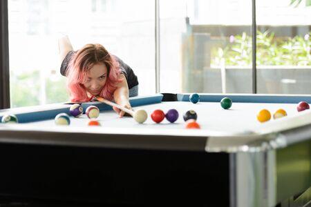 Beautiful woman with pink hair playing billiard