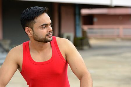 Jeune homme indien barbu pensant et regardant loin dehors