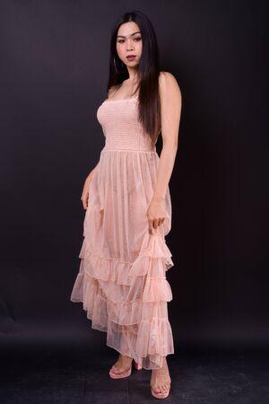 Full body shot of young beautiful Asian woman