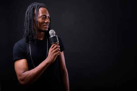 Portrait of young handsome African man with dreadlocks using microphone