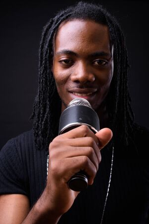 Face of young handsome African man with dreadlocks using microphone