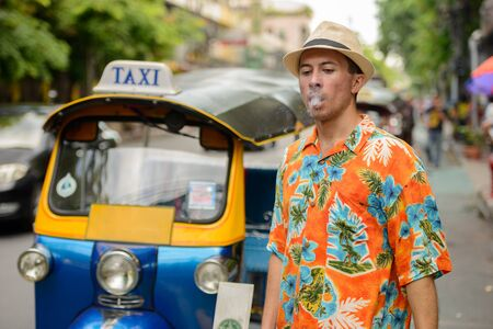 Young handsome tourist man with tuk tuk in Bangkok city