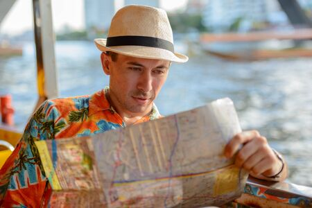 Young handsome tourist man reading map and riding boat on the river