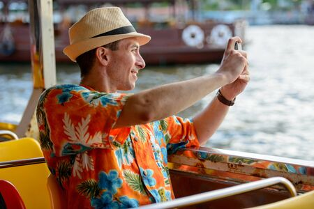 Happy young tourist man taking picture with phone while riding boat on the river