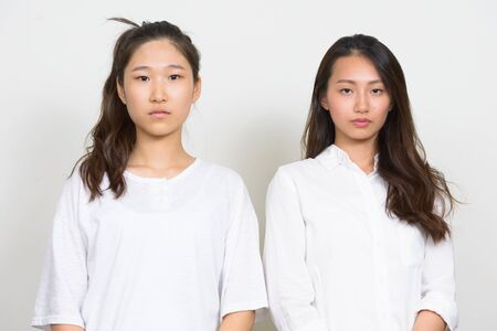 Two young beautiful Asian women as friends together