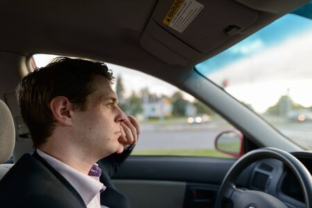 Profile view of young handsome businessman driving car in suburban street