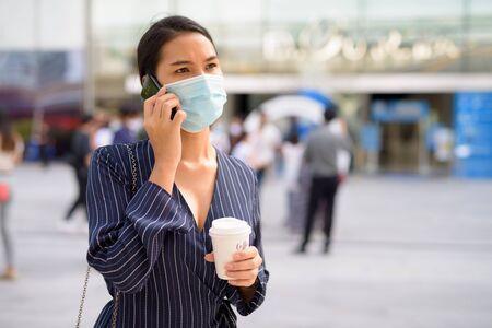 Jeune femme d'affaires asiatique avec masque parlant au téléphone tout en prenant un café sur le pouce comme la nouvelle normalité à l'extérieur
