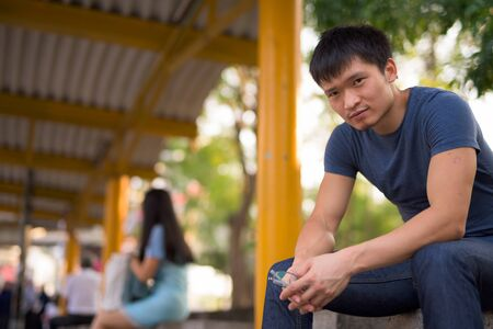 Portrait of young Asian man sitting at the bus stop