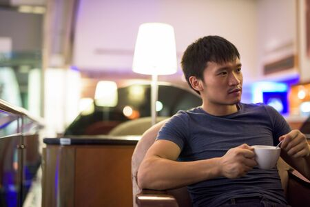 Portrait of young Asian man drinking coffee and sitting inside the mall Stok Fotoğraf