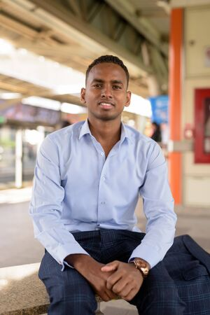 Happy young handsome African businessman smiling while sitting at the sky train station Banque d'images