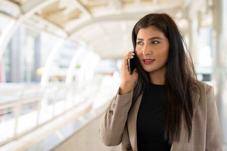 Happy young beautiful Indian businesswoman talking on the phone at footbridge in the city Zdjęcie Seryjne