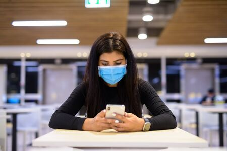Young Indian woman with mask using phone and sitting with distance at food court