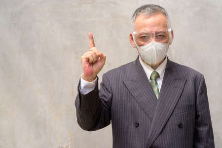 Portrait of mature Japanese businessman with mask and face shield for protection from corona virus outbreak outdoors Archivio Fotografico