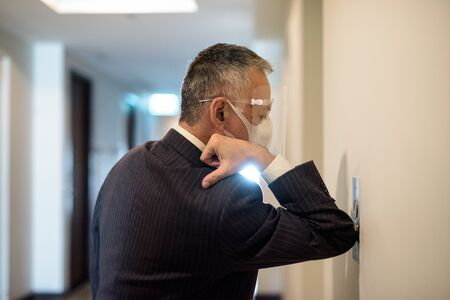 Mature Japanese businessman with mask and face shield pressing elevator button with elbow
