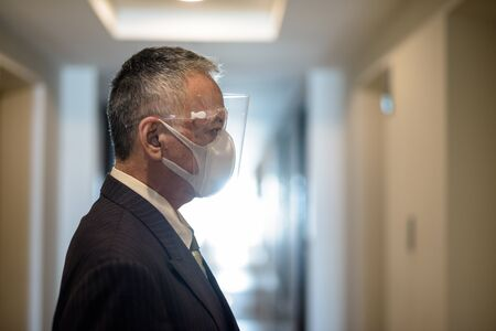 Mature Japanese businessman with mask and face shield waiting for the elevator