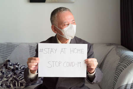 Portrait of mature Japanese businessman with mask staying at home under quarantine for corona virus covid-19 pandemic