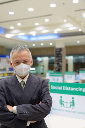 Portrait of mature Japanese businessman with mask for protection from corona virus outbreak social distancing at the food court Archivio Fotografico