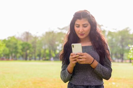 Young beautiful Indian woman using phone at the park outdoors