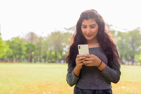 Happy young beautiful Indian woman using phone at the park outdoors