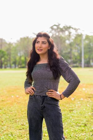 Happy young beautiful Indian woman thinking at the park outdoors