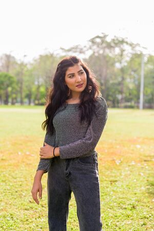 Young beautiful Indian woman thinking at the park outdoors