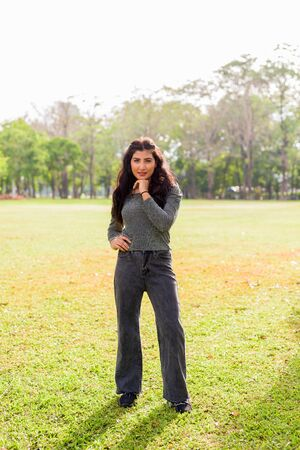 Full body shot of happy young beautiful Indian woman smiling at the park outdoors 写真素材
