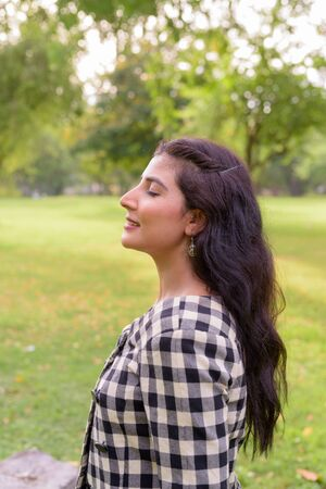 Profile view of happy young beautiful Indian woman smiling with eyes closed at the park outdoors 写真素材