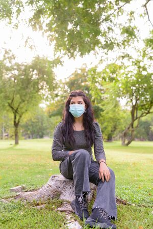 Full body shot of young Indian woman with mask thinking and sitting at the park