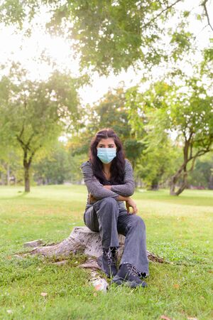 Full body shot of young Indian woman with mask sitting and relaxing at the park